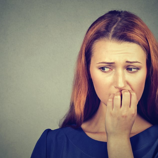 Closeup portrait young nervous woman biting her fingernails craving something or anxious, isolated on gray wall background. Negative human emotions facial expression feeling